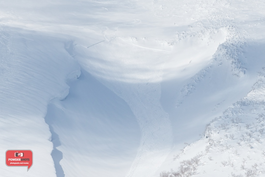 Avalanches do occur on Mount Yotei, here two snowboarders set off a loaded cornice