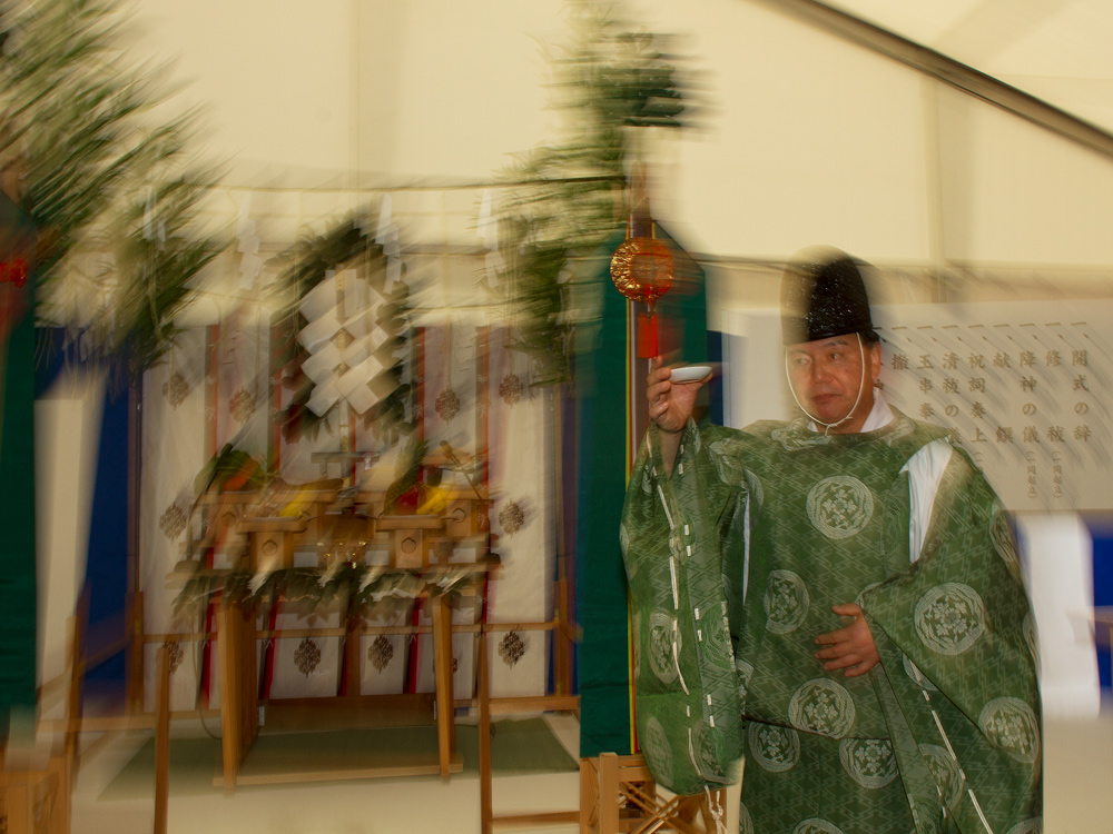 """The Shinto priest raises sake in a """"Kanpai"""" call to end the blessing."""