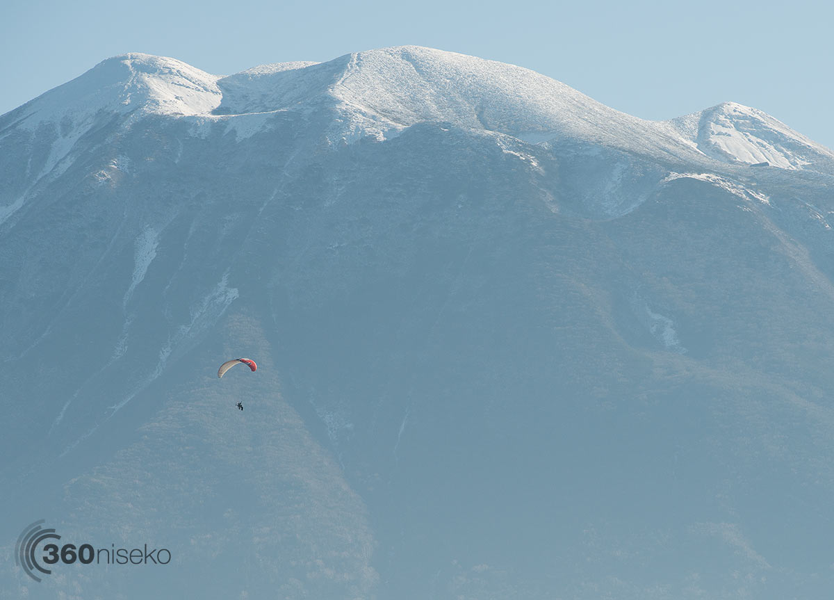Motorised paraglider cruising past Hirafu Village, 11 November 2014